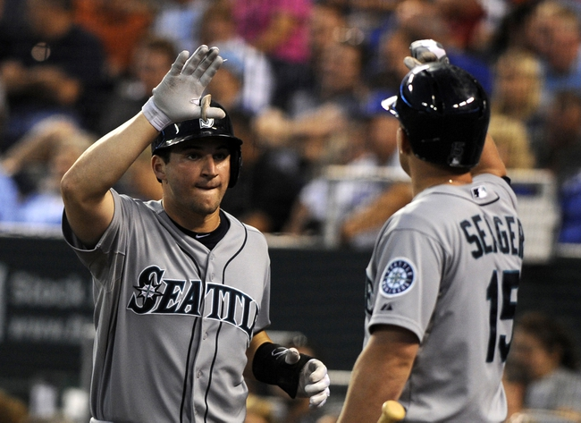 Sep 4, 2013; Kansas City, MO, USA; Seattle Mariners catcher Mike Zunino (3) is congratulated by third baseman Kyle Seager (15) after scoring against the Kansas City Royals in the third inning at Kauffman Stadium. Mandatory Credit: John Rieger-USA TODAY Sports