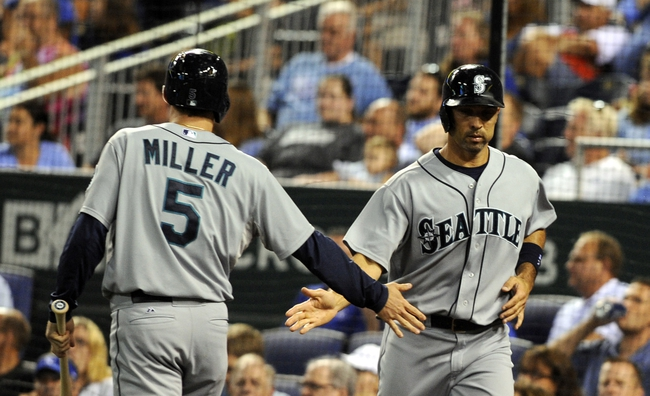 Sep 4, 2013; Kansas City, MO, USA; Seattle Mariners left fielder Raul Ibanez (28) is congratulated by shortstop Brad Miller (5) after scoring against the Kansas City Royals in the fourth inning at Kauffman Stadium. Mandatory Credit: John Rieger-USA TODAY Sports