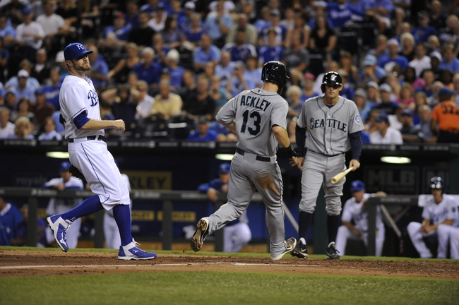 Sep 4, 2013; Kansas City, MO, USA; Seattle Mariners second baseman Dustin Ackley (13) scores on a wild pitch by Kansas City Royals relief pitcher Wade Davis (left) in the fourth inning at Kauffman Stadium. Mandatory Credit: John Rieger-USA TODAY Sports