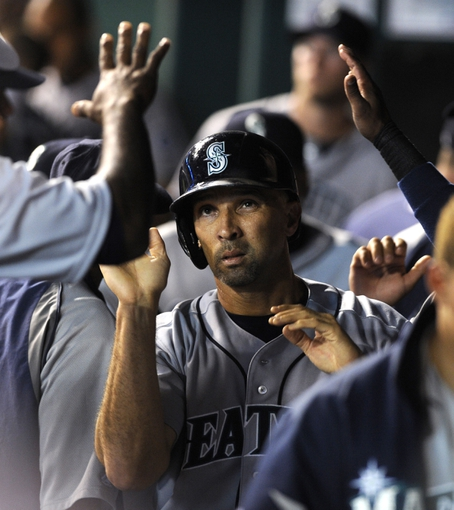 Sep 4, 2013; Kansas City, MO, USA; Seattle Mariners left fielder Raul Ibanez (28) is congratulated in the dugout after scoring against the Kansas City Royals in the fourth inning at Kauffman Stadium. Mandatory Credit: John Rieger-USA TODAY Sports