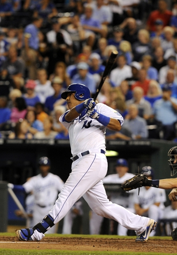 Sep 4, 2013; Kansas City, MO, USA; Kansas City Royals catcher Salvador Perez (13) drives in a run with a sacrifice fly against the Seattle Mariners in the fourth inning at Kauffman Stadium. Mandatory Credit: John Rieger-USA TODAY Sports