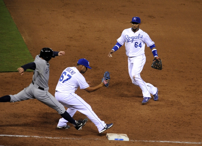 Sep 4, 2013; Kansas City, MO, USA; Kansas City Royals second baseman Emilio Bonifacio (64) tosses the ball to relief pitcher Francisley Bueno (67) covering first base against the Seattle Mariners shortstop Brad Miller (5) in the sixth inning at Kauffman Stadium. Mandatory Credit: John Rieger-USA TODAY Sports