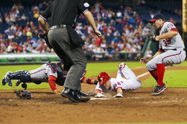 Sep 4, 2013; Philadelphia, PA, USA; Washington Nationals catcher Jhonatan Solano (23) tags out Philadelphia Phillies second baseman Chase Utley (26) at home plate during the eighth inning at Citizens Bank Park. The Nationals defeated the Phillies 3-2. Mandatory Credit: Howard Smith-USA TODAY Sports