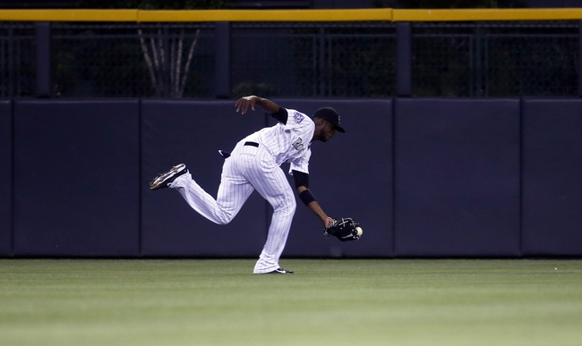 Sep 4, 2013; Denver, CO, USA; Colorado Rockies center fielder Dexter Fowler (24) catches a fly ball during the second inning against the Los Angeles Dodgers at Coors Field. Mandatory Credit: Chris Humphreys-USA TODAY Sports