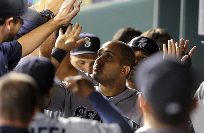 Sep 4, 2013; Kansas City, MO, USA; Seattle Mariners designated hitter Kendrys Morales (center) is congratulated in the dug out after hitting a 2 run home run against the Kansas City Royals in the ninth inning at Kauffman Stadium. Seattle won the game 6-4. Mandatory Credit: John Rieger-USA TODAY Sports