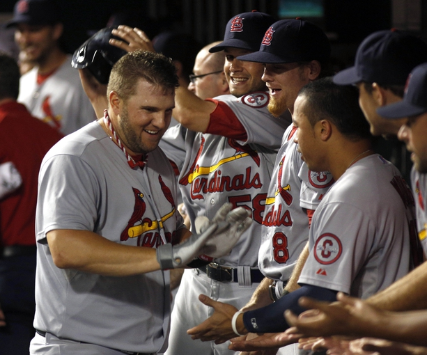 Sep 4, 2013; Cincinnati, OH, USA; St. Louis Cardinals first baseman Matt Adams, left, is congratulated by teammates after he hit a solo home run off Cincinnati Reds relief pitcher Logan Ondrusek (not pictured) in the 16th  inning at Great American Ball Park. St. Louis won 5-4. Mandatory Credit: David Kohl-USA TODAY Sports