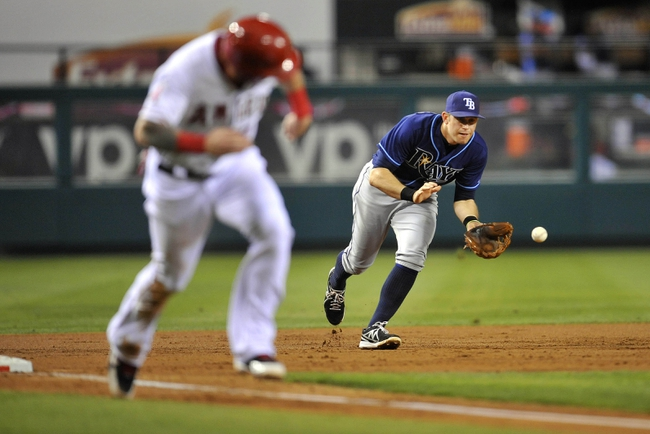 September 4, 2013; Anaheim, CA, USA; Tampa Bay Rays third baseman Evan Longoria (3) fields a ground ball as Los Angeles Angels right fielder Josh Hamilton (32) runs to home plate during the second inning at Angel Stadium of Anaheim. Mandatory Credit: Gary A. Vasquez-USA TODAY Sports