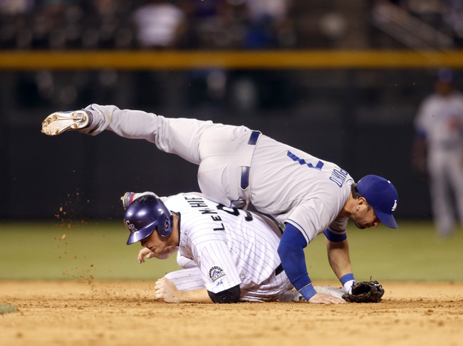 Sep 4, 2013; Denver, CO, USA; Colorado Rockies third baseman DJ LeMahieu (9) is forced out as Los Angeles Dodgers second baseman Nick Punto (7) lands on top of him attempting to turn a double play during the eighth inning at Coors Field.  The Rockies won 7-5.  Mandatory Credit: Chris Humphreys-USA TODAY Sports