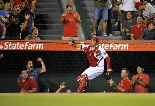September 4, 2013; Anaheim, CA, USA; Los Angeles Angels catcher Hank Conger (16) hangs on to the backstop net after catching a fly ball in foul territory in the sixth inning against the Tampa Bay Rays at Angel Stadium of Anaheim. Mandatory Credit: Gary A. Vasquez-USA TODAY Sports