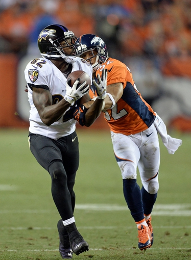 Sep 5, 2013; Denver, CO, USA; Baltimore Ravens wide receiver Torrey Smith (82) pulls in a reception as Denver Broncos defensive back Tony Carter (32) defends in the fourth quarter at Sports Authority Field at Mile High. The Broncos defeated the Ravens 49-27. Mandatory Credit: Ron Chenoy-USA TODAY Sports