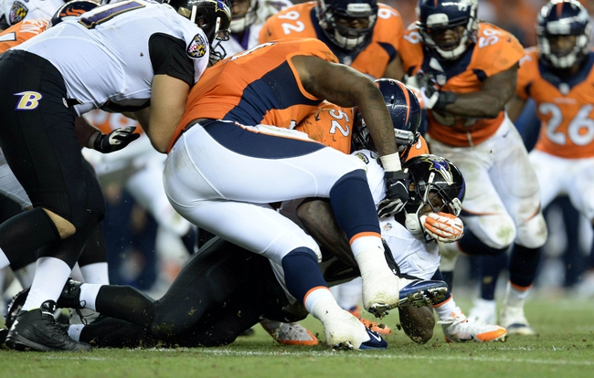 Sep 5, 2013; Denver, CO, USA;  Baltimore Ravens running back Bernard Pierce (30) is tackled by Denver Broncos defensive end Robert Ayers (91) and outside linebacker Wesley Woodyard (52) in the fourth quarter at Sports Authority Field at Mile High. The Broncos defeated the Ravens 49-27. Mandatory Credit: Ron Chenoy-USA TODAY Sports