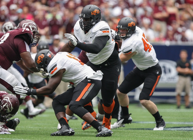 Aug 31, 2013; Houston, TX, USA; Oklahoma State Cowboys defensive tackle Calvin Barnett (99) plays defense during the first quarter against the Mississippi State Bulldogs at Reliant Stadium. Mandatory Credit: Troy Taormina-USA TODAY Sports