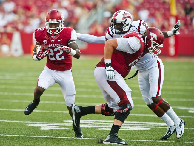 Aug 31, 2013; Fayetteville, AR, USA; Arkansas Razorback running back Nate Holmes (22) carries the ball as offensive tackle David Hurd (69) blocks Louisiana Ragin' Cajuns safety T.J. Worthy (27) during a game at Donald W. Reynolds Razorback Stadium. Arkansas defeated Louisiana 34-14. Mandatory Credit: Beth Hall-USA TODAY Sports