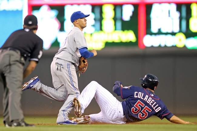Sep 6, 2013; Minneapolis, MN, USA; Toronto Blue Jays shortstop Ryan Goins (17) turns a double play as Minnesota Twins first baseman Chris Colabello (55) slides during the second inning at Target Field. Mandatory Credit: Brace Hemmelgarn-USA TODAY Sports