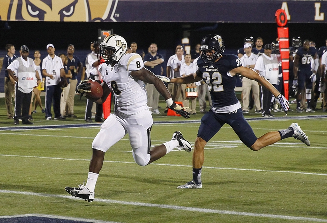Sep 6, 2013; Miami, FL, USA;  Central Florida Knights running back Storm Johnson (8) runs for a touchdown past Florida International Panthers safety Justin Halley (32) for a touchdown in the second quarter at FIU Stadium. Mandatory Credit: Robert Mayer-USA TODAY Sports