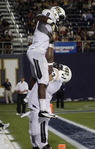 Sep 6, 2013; Miami, FL, USA;  Central Florida Knights offensive linesman Jordan McCray (63) lifts running back Storm Johnson (8) after his touchdown run against the Florida International Panthers in the second quarter at FIU Stadium. Mandatory Credit: Robert Mayer-USA TODAY Sports