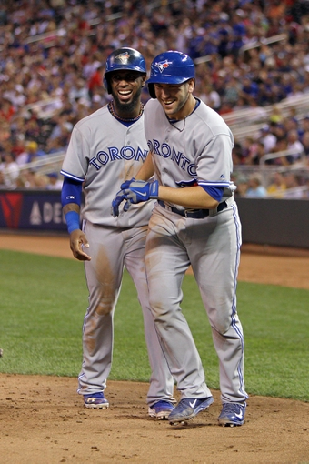 Sep 6, 2013; Minneapolis, MN, USA; Toronto Blue Jays shortstop Jose Reyes (7) laughs with catcher Josh Thole (30) after scoring a run during the third inning against the Minnesota Twins at Target Field. Mandatory Credit: Brace Hemmelgarn-USA TODAY Sports