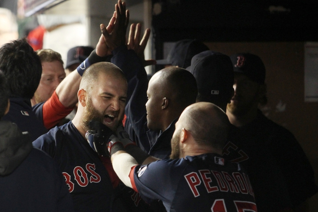 Sep 6, 2013; Bronx, NY, USA; Boston Red Sox first baseman Mike Napoli (12) has his beard pulled in celebration by Boston Red Sox second baseman Dustin Pedroia (15) after hitting a game-tying grand slam home run during the seventh inning of a game against the New York Yankees at Yankee Stadium. Mandatory Credit: Brad Penner-USA TODAY Sports