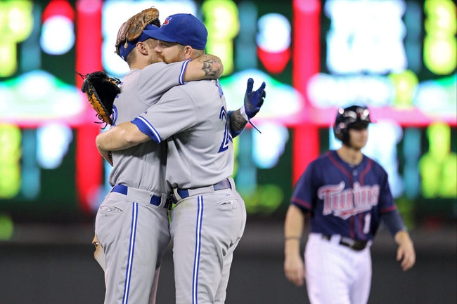 Sep 6, 2013; Minneapolis, MN, USA; Toronto Blue Jays third baseman Brett Lawrie (13) and first baseman Adam Lind (26) celebrate following the game against the Minnesota Twins at Target Field. The Blue Jays defeated the Twins 6-5. Mandatory Credit: Brace Hemmelgarn-USA TODAY Sports