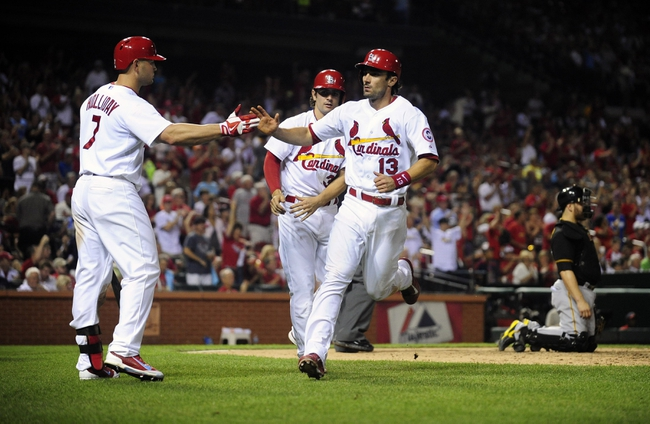 Sep 6, 2013; St. Louis, MO, USA; St. Louis Cardinals second baseman Matt Carpenter (13) is congratulated by left fielder Matt Holliday (7) after scoring on a single by center fielder Jon Jay (not pictured) during the seventh inning against the Pittsburgh Pirates at Busch Stadium. Mandatory Credit: Jeff Curry-USA TODAY Sports
