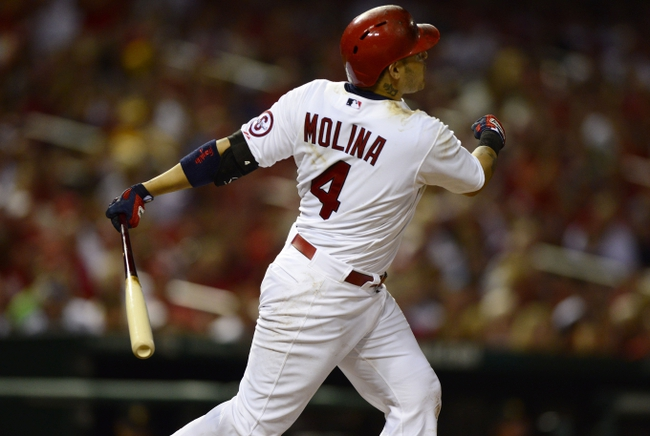 Sep 6, 2013; St. Louis, MO, USA; St. Louis Cardinals catcher Yadier Molina (4) hits a three run home run off of Pittsburgh Pirates relief pitcher Bryan Morris (not pictured) during the seventh inning at Busch Stadium. Mandatory Credit: Jeff Curry-USA TODAY Sports