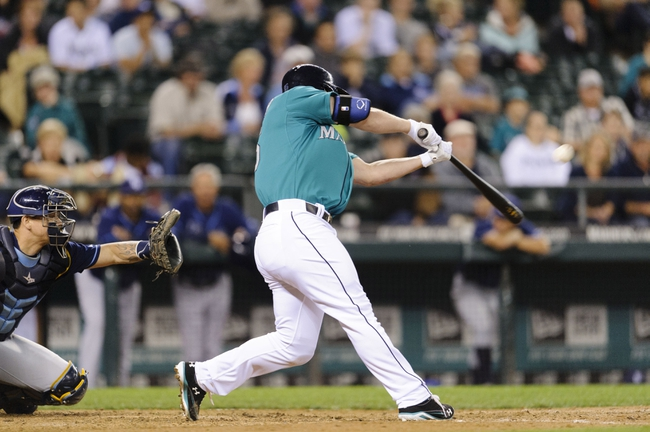 Sep 6, 2013; Seattle, WA, USA; Seattle Mariners third baseman Kyle Seager (15) hits a fly ball which drops as a Tampa Bay Rays error during the 8th inning at Safeco Field. Seattle defeated Tampa Bay 6-4. Mandatory Credit: Steven Bisig-USA TODAY Sports