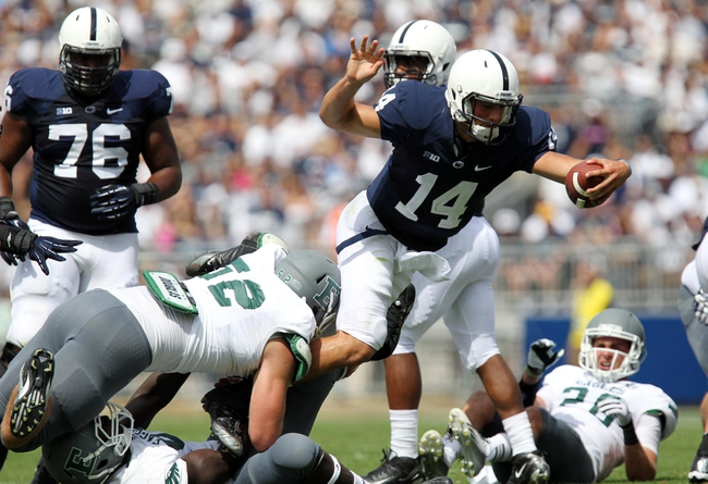 Sep 7, 2013; University Park, PA, USA; Penn State Nittany Lions quarterback Christian Hackenberg (14) jumps over the Eastern Michigan Eagles defense during the second quarter at Beaver Stadium. Mandatory Credit: Matthew O'Haren-USA TODAY Sports