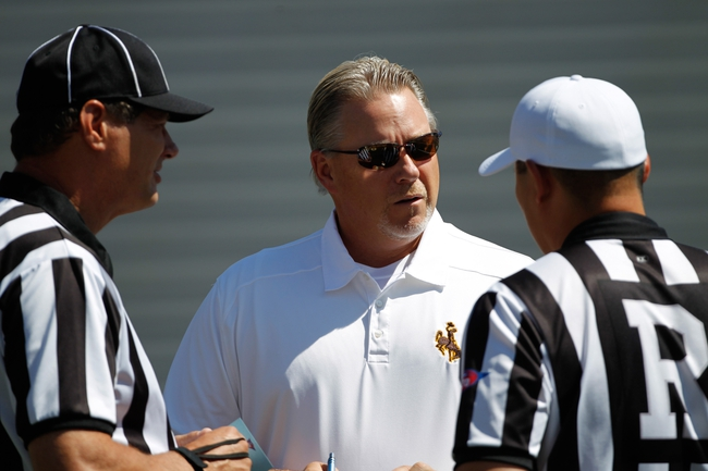 Sep 7, 2013; Laramie, WY, USA; Wyoming Cowboys head coach Dave Christensen visits with referees before the game between the Wyoming Cowboys and the Idaho Vandals at War Memorial Stadium. Mandatory Credit: Troy Babbitt-USA TODAY Sports