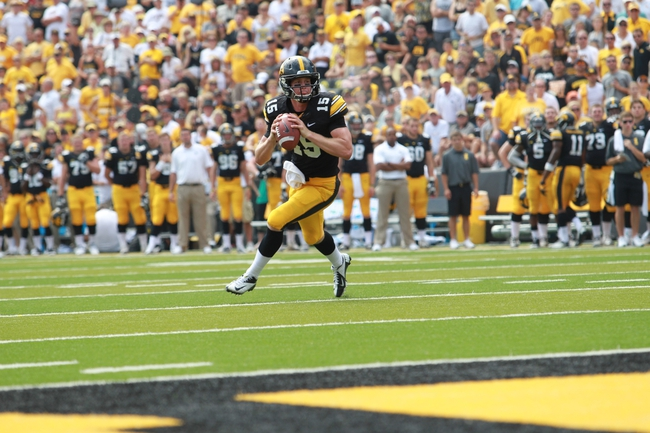 Sep 7, 2013; Iowa City, IA, USA; Iowa Hawkeyes quarterback Jake Rudock (15) rolls out to pass against the Missouri State Bears at Kinnick Stadium.  Iowa beat Missouri State 28-14.  Mandatory Credit: Reese Strickland-USA TODAY Sports