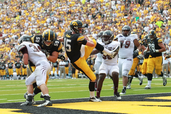 Sep 7, 2013; Iowa City, IA, USA; Iowa Hawkeyes quarterback Jake Rudock (15) is hit late in the end zone by  Missouri State Bears safety Jeremiah Plowden (30) at Kinnick Stadium.  Iowa beat Missouri State 28-14.  Mandatory Credit: Reese Strickland-USA TODAY Sports