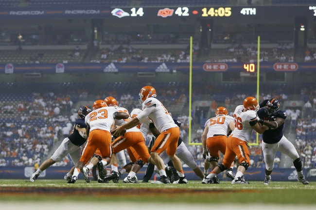 Sep 7, 2013; San Antonio, TX, USA; Oklahoma State Cowboys quarterback Chelf, Clint (10) hands off the ball to running back Childs, Rennie (23) during the second half against the Texas-San Antonio Roadrunners at Alamodome. Oklahoma State Cowboys beat Texas-San Antonio Roadrunners 56-35. Mandatory Credit: Soobum Im-USA TODAY Sports