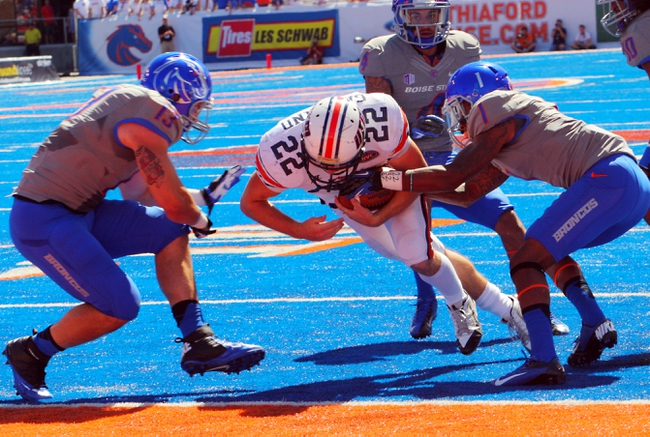Sep 7, 2013; Boise, ID, USA; Tennessee Martin Skyhawks running back Trent Garland (22) runs the ball between Boise State Broncos linebacker Blake Renaud (13) and  cornerback Bryan Douglas (1) for a touchdown during the first half at Bronco Stadium. Mandatory Credit: Brian Losness-USA TODAY Sports