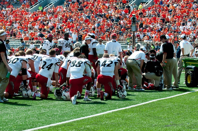 Sep 7, 2013; Champaign, IL, USA; Cincinnati Bearcats huddle while Cincinnati Bearcats quarterback Munchie Legaux (4) is attended to after a leg injury during the fourth quarter against the Illinois Fighting Illini at Memorial Stadium. Illinois won 45-17.  Mandatory Credit: Bradley Leeb-USA TODAY Sports