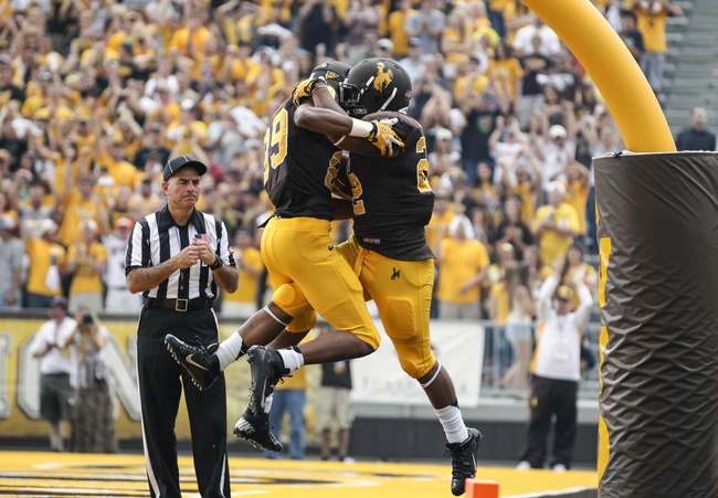Sep 7, 2013; Laramie, WY, USA; Wyoming Cowboys running back Tedder Easton (22) celebrates with teammate Nico Brown (89) after scoring a touchdown against the Idaho Vandals during the second quarter at War Memorial Stadium. Mandatory Credit: Troy Babbitt-USA TODAY Sports