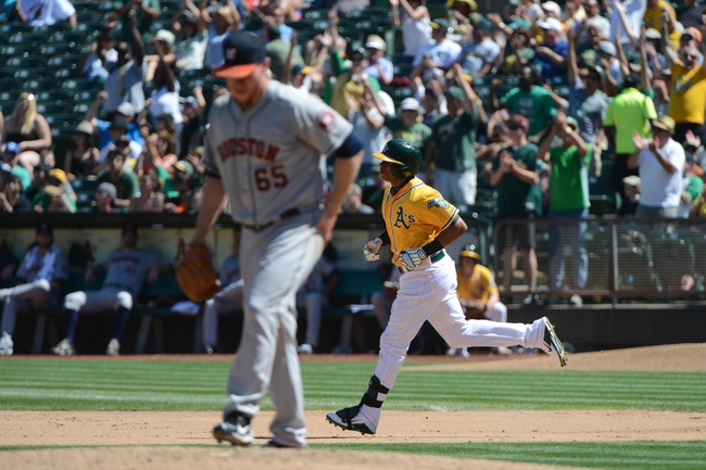 September 7, 2013; Oakland, CA, USA; Oakland Athletics left fielder Yoenis Cespedes (52, right) rounds the bases after hitting a solo home run off of Houston Astros starting pitcher Brett Oberholtzer (65, left) during the fourth inning at O.co Coliseum. Mandatory Credit: Kyle Terada-USA TODAY Sports