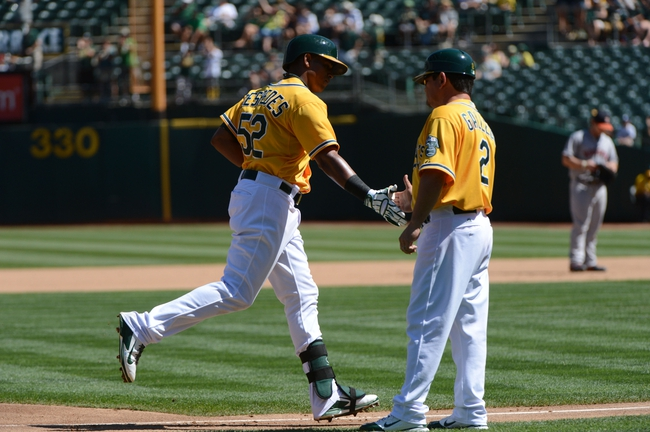 September 7, 2013; Oakland, CA, USA; Oakland Athletics left fielder Yoenis Cespedes (52) is congratulated by third base coach Mike Gallego (2) for hitting a solo home run against the Houston Astros during the fourth inning at O.co Coliseum. Mandatory Credit: Kyle Terada-USA TODAY Sports