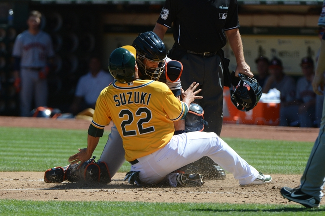 September 7, 2013; Oakland, CA, USA; Oakland Athletics catcher Kurt Suzuki (22) is tagged out by Houston Astros catcher Matt Pagnozzi (44, center) during the third inning at O.co Coliseum. Mandatory Credit: Kyle Terada-USA TODAY Sports
