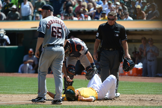 September 7, 2013; Oakland, CA, USA; Oakland Athletics catcher Kurt Suzuki (22, bottom) reacts after being tagged out by Houston Astros catcher Matt Pagnozzi (44, center) during the third inning at O.co Coliseum. Mandatory Credit: Kyle Terada-USA TODAY Sports