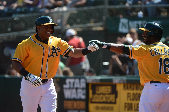 September 7, 2013; Oakland, CA, USA; Oakland Athletics left fielder Yoenis Cespedes (52, left) is congratulated by second baseman Alberto Callaspo (18) for hitting a solo home run against the Houston Astros during the fourth inning at O.co Coliseum. Mandatory Credit: Kyle Terada-USA TODAY Sports