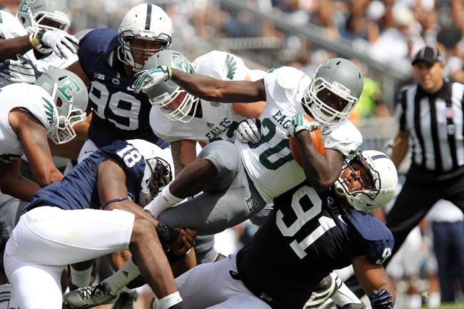 Sep 7, 2013; University Park, PA, USA; Eastern Michigan Eagles running back Bronson Hill (30) leaps over Penn State Nittany Lions defensive tackle DaQuan Jones (91) during the third quarter at Beaver Stadium. Penn State defeated Eastern Michigan 45-7. Mandatory Credit: Matthew O'Haren-USA TODAY Sports