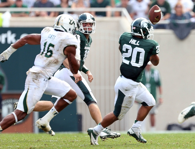 Sep 7, 2013; East Lansing, MI, USA; Michigan State Spartans running back Nick Hill (20) attempts to grab shovel pass from Michigan State Spartans quarterback Andrew Maxwell (10) during the 2nd half at Spartan Stadium. MSU won 21-6. Mandatory Credit: Mike Carter-USA TODAY Sports