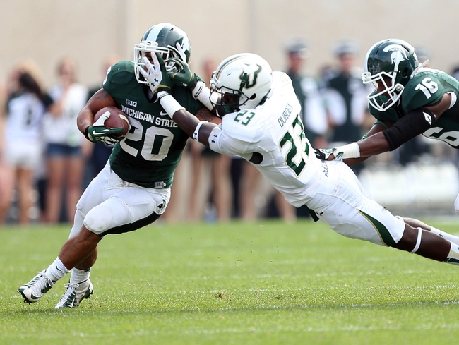 Sep 7, 2013; East Lansing, MI, USA; Michigan State Spartans running back Nick Hill (20) has face mask grabbed by South Florida Bulls defensive back Kenneth Durden (23)during the 2nd half at Spartan Stadium. MSU won 21-6. Mandatory Credit: Mike Carter-USA TODAY Sports