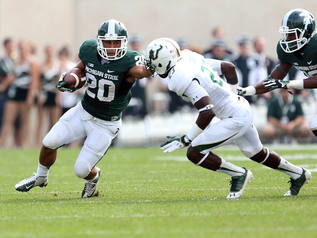 Sep 7, 2013; East Lansing, MI, USA; Michigan State Spartans running back Nick Hill (20) stiff arms South Florida Bulls defensive back Kenneth Durden (23) during the 2nd half at Spartan Stadium. MSU won 21-6. Mandatory Credit: Mike Carter-USA TODAY Sports
