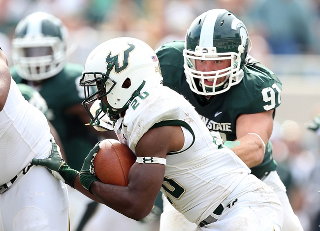 Sep 7, 2013; East Lansing, MI, USA; South Florida Bulls running back Marcus Shaw (20) is tackled by Michigan State Spartans defensive tackle Tyler Hoover (91) during the 2nd half at Spartan Stadium. MSU won 21-6. Mandatory Credit: Mike Carter-USA TODAY Sports