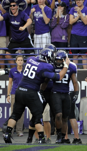 Sep 7, 2013; Evanston, IL, USA; Northwestern Wildcats running back Treyvon Green (22) is greeted by offensive linesman Brandon Vitabile (66) after scoring a touchdown against the Syracuse Orange during the first quarter at Ryan Field. Mandatory Credit: David Banks-USA TODAY Sports