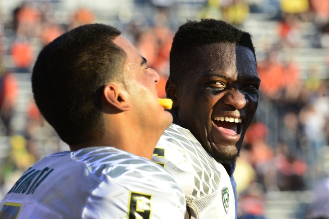 Sep 7, 2013; Charlottesville, VA, USA; Oregon Ducks quarterback Marcus Mariota (8) reacts on the bench with  linebacker Boseko Lokombo (25) late in the fourth quarter. The Ducks defeated the Virginia Cavaliers 59-10 at Scott Stadium. Mandatory Credit: Bob Donnan-USA TODAY Sports