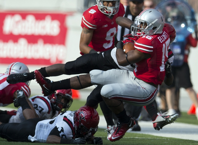 Sep 7, 2013; Columbus, OH, USA; Ohio State Buckeyes running back Ezekiel Elliott (15) is tackled by San Diego State Aztecs defensive backs Nat Berhe (20) and King Holder (35) at Ohio Stadium. Ohio State won the game 42-7. Mandatory Credit: Greg Bartram-USA TODAY Sports