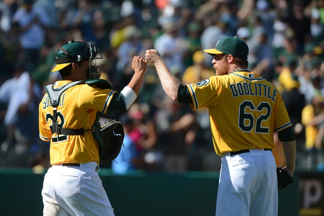 September 7, 2013; Oakland, CA, USA; Oakland Athletics catcher Kurt Suzuki (22, left) and relief pitcher Sean Doolittle (62) celebrate after the game against the Houston Astros at O.co Coliseum. The Athletics defeated the Astros 2-1. Mandatory Credit: Kyle Terada-USA TODAY Sports