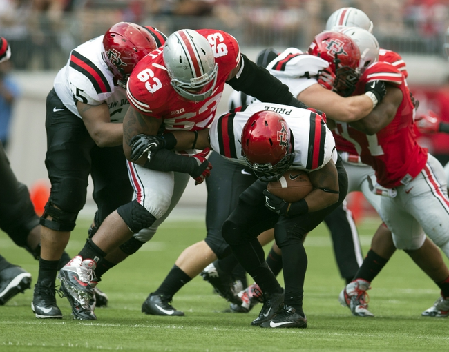 Sep 7, 2013; Columbus, OH, USA; San Diego State Aztecs running back Chase Price (22) tries to spin away from Ohio State Buckeyes defensive lineman Michael Bennett (63) at Ohio Stadium. Ohio State won the game 42-7. Mandatory Credit: Greg Bartram-USA TODAY Sports