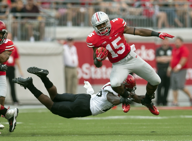 Sep 7, 2013; Columbus, OH, USA; Ohio State Buckeyes running back Ezekiel Elliott (15) is tackled by diving San Diego State Aztecs defensive back Nat Berhe (20) at Ohio Stadium. Ohio State won the game 42-7. Mandatory Credit: Greg Bartram-USA TODAY Sports